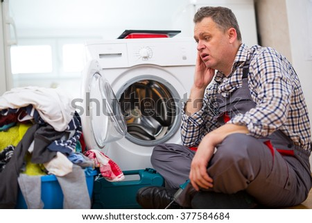 Handsome repairman repairing washing machine in kitchen. Sitting next to dirty laundry #377584684