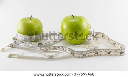 Green apple with Measuring tape on white background in concept of healthy and diet #377599468