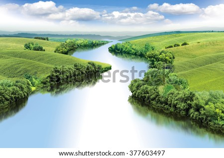 Zigzag river flows between summer valleys.a Royalty-Free Stock Photo #377603497