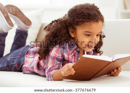 Cute little Afro-American girl in casual clothes reading a book and smiling while lying on a sofa in the room. #377676679