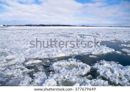 Cold, Saint-Lawrence river water with floating ice chunks between Saint-Ignace-de-Loyola and Sorel-Tracy, Québec, Canada. #377679649