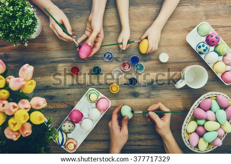 Happy easter! A mother, father and their daughter painting Easter eggs. Happy family preparing for Easter.  Royalty-Free Stock Photo #377717329