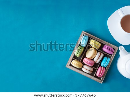 Colorful French macaroons in a wooden gift box. Cup of tea and teapot. Top view. #377767645