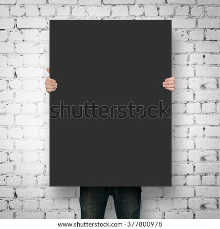 Man holding black poster mockup over brick wall #377800978