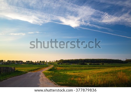 Evening rural landscape with road, field grass and beautiful blue sky. #377879836