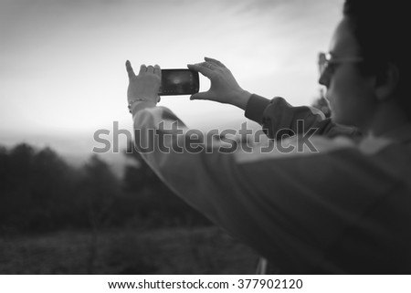 Girl in sunset taking photo with mobile phone #377902120