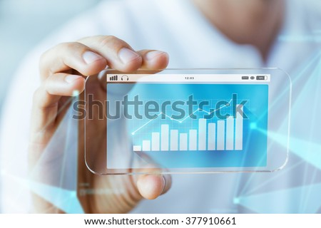 business, technology and people concept - close up of male hand holding and showing transparent smartphone with diagram chart on screen #377910661