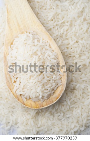 food background. brown rice in a wooden spoon. top view #377970259