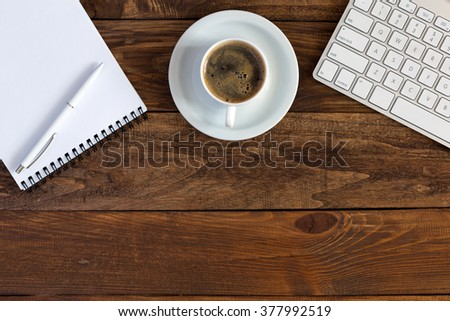 Business Composition with cropped Computer Keyboard Notepad and Pen Cup of Coffee and blank Business Card on natural Hardwood Table #377992519
