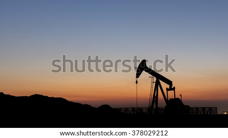 Silhouette of oil pump from oil field.