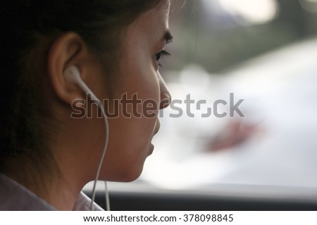 Silhouette edge Asian girl sitting in the car listening to music from smartphone in-Thailand. #378098845