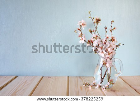 spring bouquet of flowers on the wooden table with mint background. vintage filtered image  #378225259
