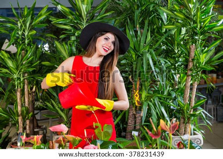 care of plants , woman gardener, woman in red dress #378231439