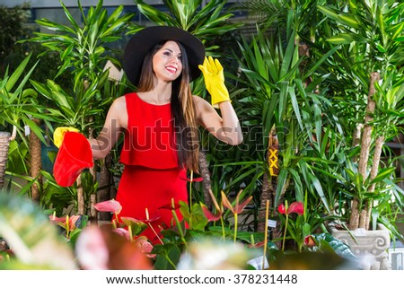 care of plants , woman gardener, woman in red dress #378231448