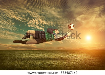 Soccer player with ball in action outdoors. #378487162