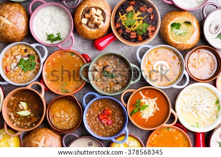 High Angle View of Various Comforting and Savory Gourmet Soups Served in Bread Bowls and Handled Dishes and Topped with Variety of Garnishes on Table Surface with Gray Tablecloth #378568345