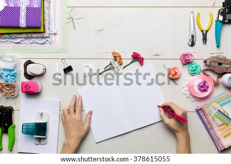 Top view of table with elements for scrapbooking, tools for decoration and handmade albums and hands of master. Royalty-Free Stock Photo #378615055