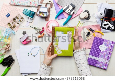 Top view of table with elements for scrapbooking, tools for decoration and handmade albums and hands of master. Royalty-Free Stock Photo #378615058