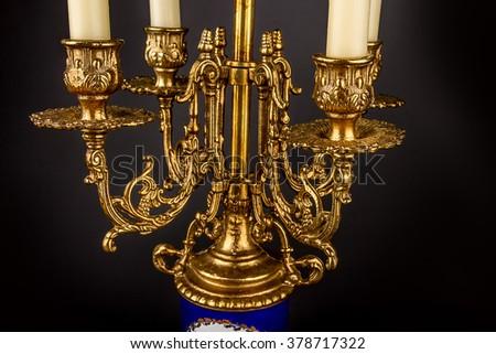 Antique bronze candelabrum - candle on a black background. Detail #378717322