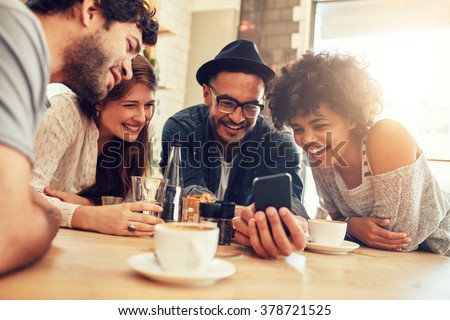 Portrait of cheerful young friends looking at smart phone while sitting in cafe. Mixed race people sitting at a table in restaurant using mobile phone. Royalty-Free Stock Photo #378721525