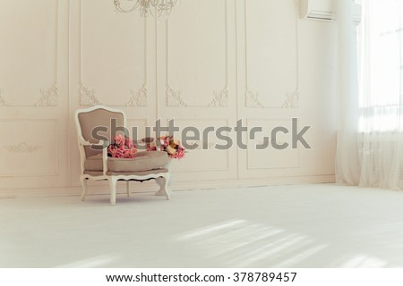 luxury interiors in beige tones. Elegant vintage armchair in a spacious room with a wall decorated with ornaments. colorful flowers in a vase standing on the wooden floor #378789457