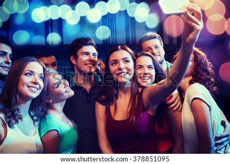 party, technology, nightlife and people concept - smiling friends with smartphone taking selfie in club #378851095