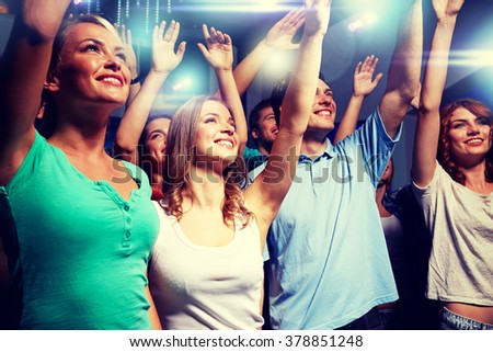 party, holidays, celebration, nightlife and people concept - smiling friends waving hands at concert in club #378851248