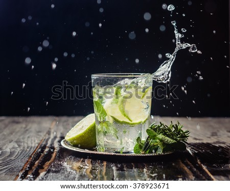 lime lemonade with rosemary and ice on a dark background in glass transparent glass. drink in motion, spray, motion #378923671