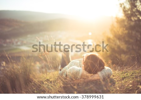 Carefree happy woman lying on green grass meadow on top of mountain edge cliff enjoying sun on her face.Enjoying nature sunset.Freedom.Enjoyment.Relaxing in mountains at sunrise.Sunshine.Daydreaming Royalty-Free Stock Photo #378999631