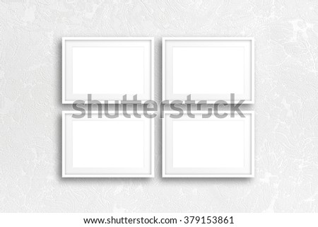 Four blank photo frames on modern textured wallpaper