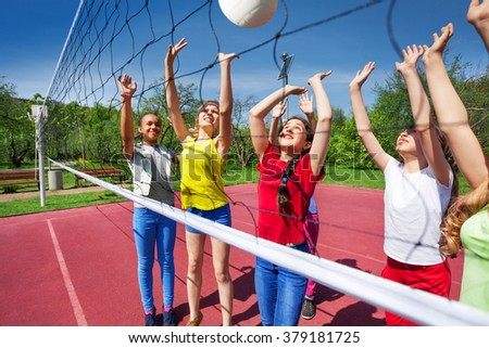 Teens playing actively near the volleyball net #379181725