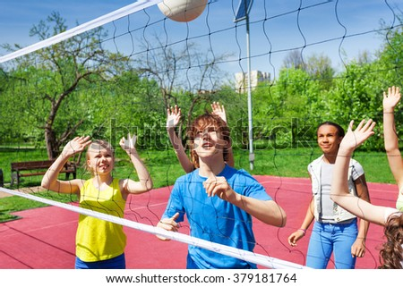 Teenagers are playing volleyball near the net #379181764