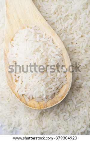 food background. brown rice in a wooden spoon. top view #379304920