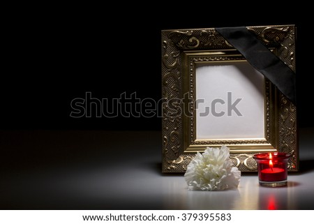 golden mourning frame with flower and candle on dark background