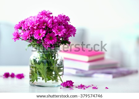 Beautiful flowers in vase on table in room #379574746