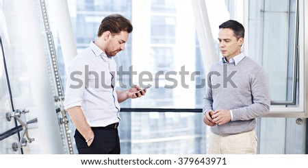 two business executives working together responding to a business situation. #379643971