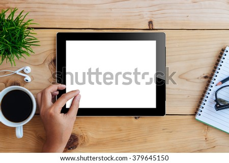 hand using mockup tablet similar to ipad style on wood desk white display with clipping path screen easy add image