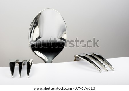 Spoon and two forks formed into conceptual figure Royalty-Free Stock Photo #379696618