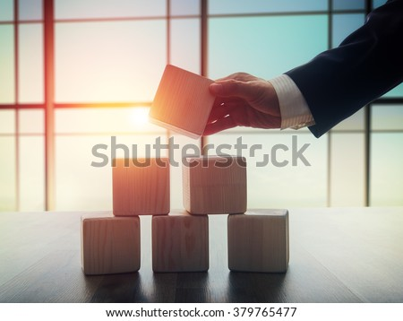 The concept of planning in business. Wooden cubes on a desk in the office. The concept of leadership. Hand men in business suit holding the cubes. Royalty-Free Stock Photo #379765477
