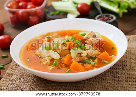 Tomato chicken soup with pumpkin, beans and celery in white bowl #379793578