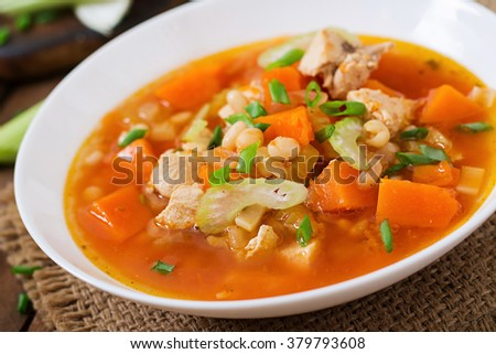 Tomato chicken soup with pumpkin, beans and celery in white bowl #379793608