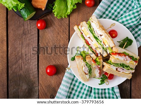 Club sandwich with cheese, cucumber, tomato, ham and eggs. Top view #379793656