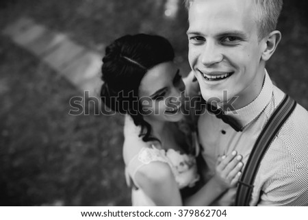 groom gently embraces her groom in the forest #379862704