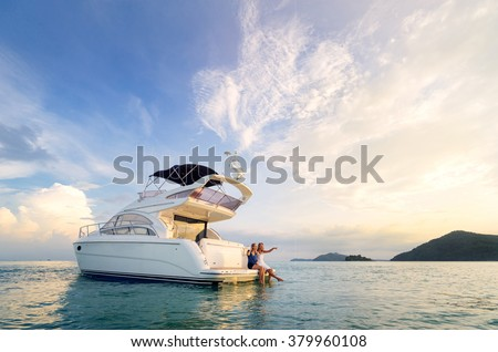 Friendship and luxury vacation. Two happy young women sitting on the yacht deck looking and pointing away sailing the sea. Royalty-Free Stock Photo #379960108