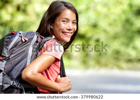 Happy young Asian Chinese backpack girl student. Cute adult woman backpacker smiling at camera with school bag doing summer backpacking travel in nature. #379980622