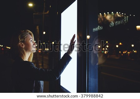 Young woman tourist using modern digital display with blank copy space screen for your text message or content, pretty female watching movement of buses on electronic bulletin board in unfamiliar city #379988842
