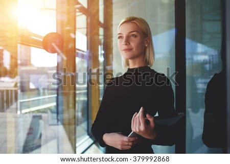 Young elegant woman thinking something while standing with touch pad near office window outside, female employer holding digital tablet while looking forward to meeting with international partners #379992868