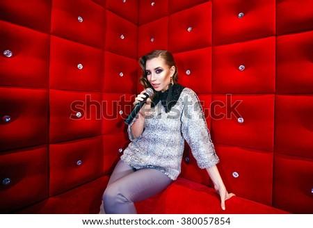 beautiful girl singing karaoke in a nightclub #380057854