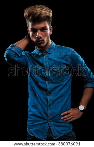 interesting young man in casual jeans shirt posing in dark studio background with hand behind his neck #380076091