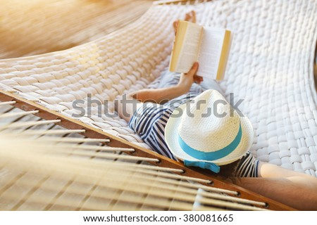 Lazy time. Man in hat in a hammock with book on a summer day #380081665